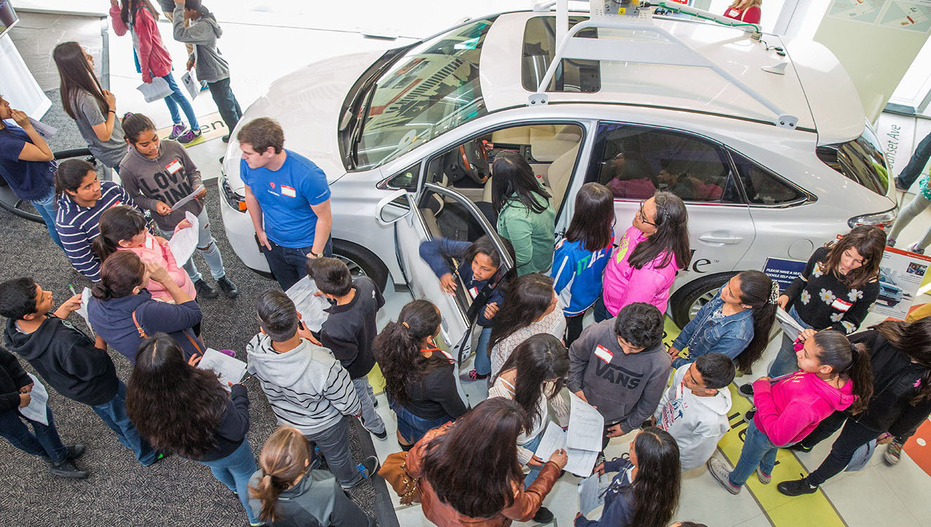 Students explore the Google self-driving car in the Museum's exhibition, <em>Where To? A History of Autonomous Vehicles</em>.